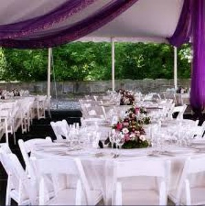 Decorated tables inside an event tent draped with colored cloth with matching centerpieces