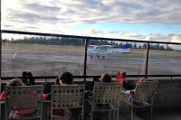 Kids watching the planes at the Gig Harbor airport, pub, food, view, airplanes, runway, eat, party, family fun, celebrate, drink, wedding, Front of Hub- from Parking Lot with airport control tower, restaurant,food, eat, good food, fun, beer, pizza, view, airplanes, airport, bar, pub, music, entertainment, free parking, events, band, weddings, parties, celebration, outdoor venue, indoor venue, cooking, service, community, local, craft, micro beer, Olympic, Gig Harbor, South Sound, Pierce County, sunset, taco Tuesday, kid friendly, family friendly , birthday, dessert, wedding rehearsal dinners, lunch, breakfast, buffet, private events, rentals, venue, events