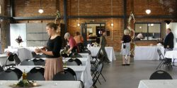 Venue being serviced by Amato Catering, Italian cuisine, food, tables set with white linens, serving guests